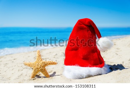 Close up Santa hat with starfish on the beach by the ocean - Christmas and new year concept #153108311