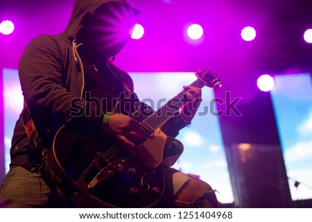 Close up scene of electric guitar player on performing stage during playing solo on concert with colourful scenic illumination via powerful lights. Unicolor simple photography #1251404968