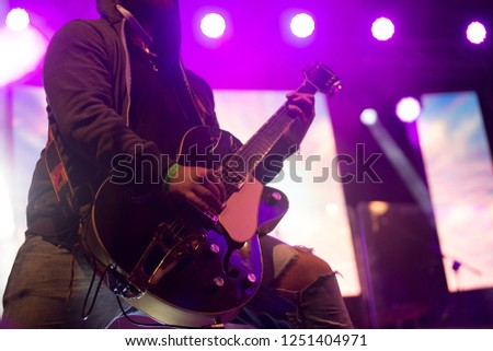 Close up scene of electric guitar player on performing stage during playing solo on concert with colourful scenic illumination via powerful lights. Unicolor simple photography #1251404971