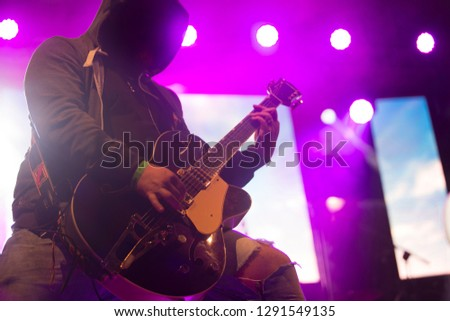 Close up scene of electric guitar player on performing stage during playing solo on concert with colourful scenic illumination via powerful lights. Unicolor simple photography #1291549135