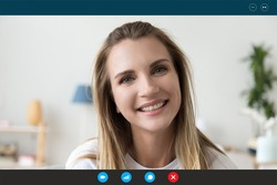 Close up screen application view of smiling young woman chat talk on video call with husband or relative, happy millennial female laugh communicate online using Webcam and wireless Internet at home