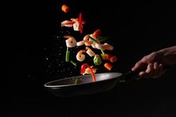 close-up, Seafood, chef cooks shrimps with fresh bright vegetables in a frying pan, roasts. on a black background for design, menus, restaurants, oriental cuisine, healthy food. horizontal photo