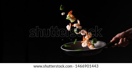 close-up, Seafood, chef cooks shrimps with pod beans and Brussels sprouts in a frying pan and fry. on a black background for design, menus, restaurants, oriental cuisine, healthy food. Banner