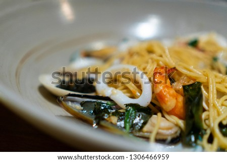 Close up seafood spaghetti with squid shrimp and big mussel serve with basil asia style at rooftop restaurant using for copy space or background food menu