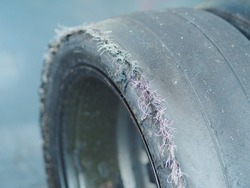 Close up selective focus of damage used slick tyre in drive. Broken car tyre with protruding cord.
