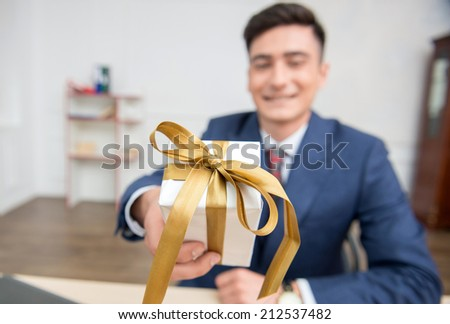 Close-up selective focus on a gift box in hands of young businessman in office working on his computer,showing a box to the camera