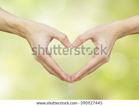 close up/selective focus on man hands make heart over blurred bright green color with bokeh light background for healthy life and good healthcare concept.