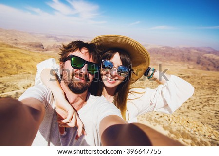 Close up self portrait , happy  hipster  couple  traveling , Handsome man with beard and young pretty cheerful girl making selfie . Jordan desert .Hikers enjoying  amazing view.
