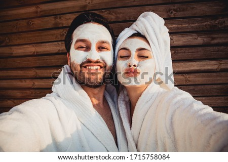 Close up selfie of beautiful happy couple after shower with a towel on head sending air kiss with cream mask on face.Woman with clay mask taking selfie with mobile phone at home enjoying relaxation.