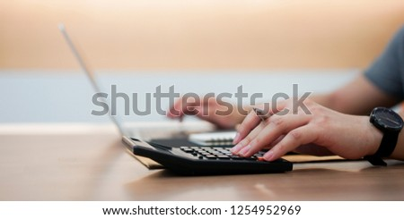 close up senior accountant employee man hand pressing on calculator and typing keyboard on laptop for input data to program at office desk for summary about payroll monthly concept