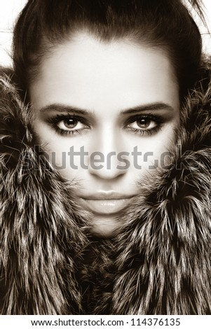 Close-up sepia portrait of young beautiful woman with stylish make-up and fur around her face