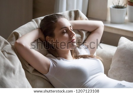 Close up serene tranquil woman smiling lying on couch at home or hotel room girl has break after work or study closing eyes putting hands behind head relax think, feels happy breath fresh air concept #1207123108