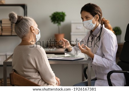 Close up serious doctor wearing medical face mask consulting mature woman patient at appointment in office, physician explaining treatment, giving recommendations, elderly generation healthcare