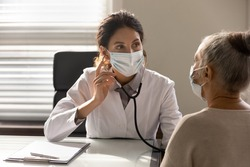 Close up serious female doctor wearing face mask and coat checking senior patient lungs, listening to heartbeat, mature woman breath, elderly generation healthcare, medical checkup concept