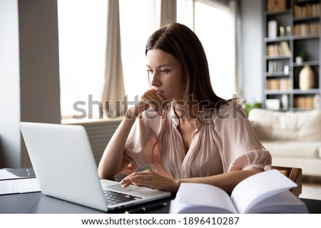 Close up serious focused woman looking at laptop screen, touching chin, sitting at desk, home office, thoughtful businesswoman pondering strategy, working on online project, searching information