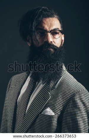Close up Serious Man with Long Beard and Mustache, Wearing Formal Checkered Suit, Looking to the Right of the Frame on a Black Background.