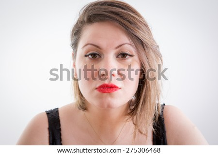 Close up Serious Portrait of a Young Blond Woman with Makeup Sadly Staring at the Camera on a Light Gray Background. #275306468