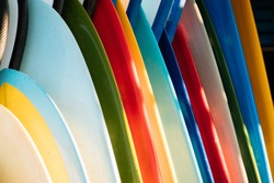 Close up Set of different color surf boards in a stack on sandy beach for rent. Multicolored surfboards as rainbow.