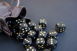 Close-up set of gaming dice rolled out of leather bag on dark background. Concept with copy space for games. Top view.