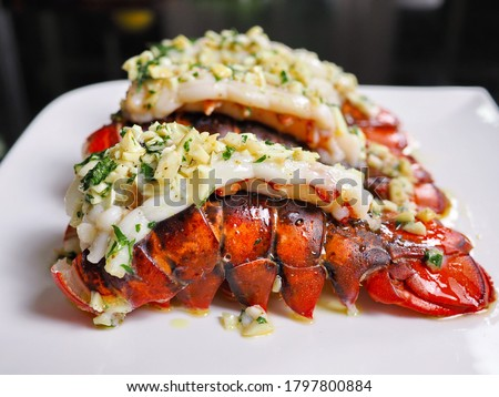 Photo of  Close up several red orange color arranged garlic butter lobster tails with parley baked for dinner at home