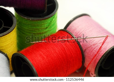 Close up sewing threads and needle on white background