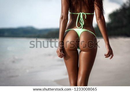 Close-up sexy ass of sporty girl wearing green swimsuit at the beach. Part of women body. Tanned booties of young model in bikini.