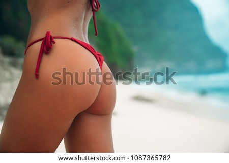 Close-up sexy ass of sporty girl wearing red swimsuit at the beach. Part of women body. Tanned booties of young model in bikini.