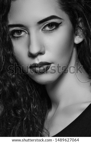 Close-up sexy woman face. Black white photo. Professional makeup. Sensual lips. Italian style image. Attractive young woman brunette with wavy hairstyle. Ideal healthy skin. Sensuality and mystery.