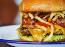 Close up, shallow depth of field photo of cheeseburger loaded with melting cheese, shoestring fries, applewood smoked bacon, ketchup, lettuce, with a brioche bun sitting on white place with blue rim.