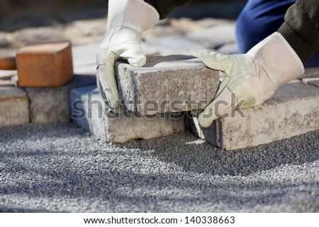 Close up shit of construction worker paving the brick road