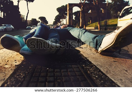 close up shoes of two people lying on the curb between two roads in Rome