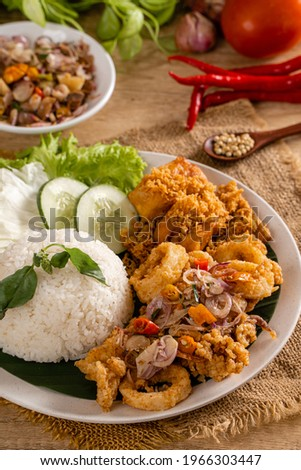 Close up Shoot A Set of fried squid with Sambal Matah and indonesian Spicies or A set of 'Cumi Goreng Sambal Matah '. Cumi Goreng Sambal Matah is Indonesian cuisine.  Stock fotó ©