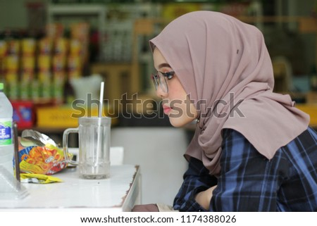 close up shoot of an Asian girl wearing hijab at open café in the park. #1174388026