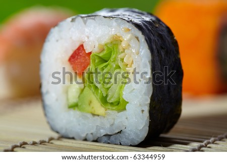 Close-up shoot of delicious maki sushi with nori, avocado and salad. Traditional Asian food.