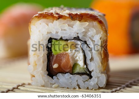 Close-up shoot of delicious maki sushi with smoked eel, avocado and salmon. Traditional Asian food.