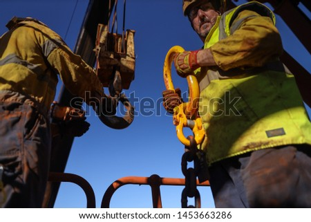 Close up shoot of male rigger wearing safety helmet safety glove personnel safety protective equipment holding crane lifting chain hook, during shut down operation construction site Perth, Australia