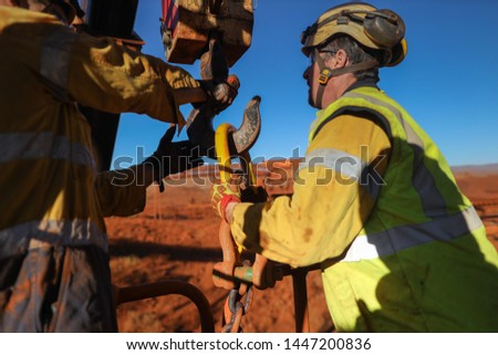 Close up shoot of male riggers wearing safety helmet holding and conducting crane lifting chain hook into crane lifting lug during shut down operation construction site
