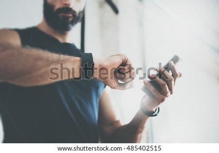 Close-up Shot Bearded Sportive Man After Workout Session Checks Fitness Results Smartphone.Adult Guy Wearing Sport Tracker Wristband Arm.Training hard inside gym.Horizontal bar background.Blurred #485402515