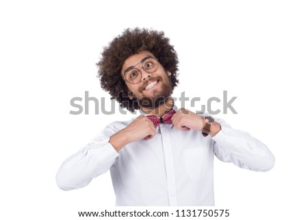 Close-up shot crazy man smiling cross eyed touches the bow he wears wearing glasses with curly hairstyle isolated on a white background. #1131750575