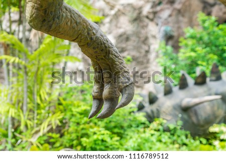 Close up shot from a Hand, claw of dinosaur (theropod) on green jungle with stegosaurus background.
