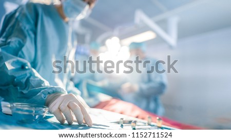 Close-up Shot in Operating Room of Surgical Table with Instruments, Assistant Picks up Instruments for Surgeons During Operation. Surgery in Progress. Professional Medical Doctors Performing Surgery.