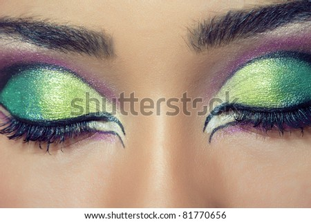 Close-up shot of a beautiful young woman's face with colorful eye make-up