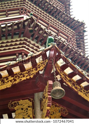 Close up shot of a bell hanging from the corner of a buddhist temple in Guangzhou, China  #1072467041