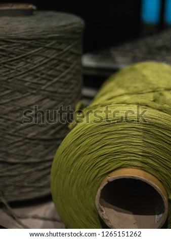 Close-up shot of a big  green thread spool, with grey spool in background #1265151262