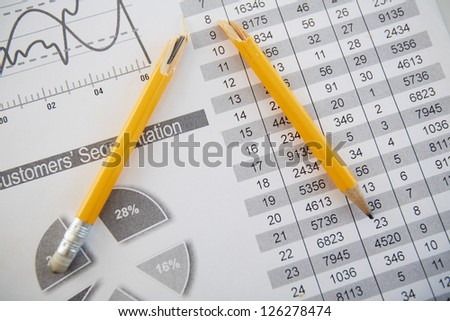 Close-up shot of a broken pencil lying over printed statistics