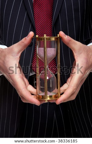 Close up shot of a businessman holding a brass sand timer or hourglass