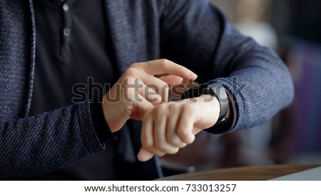 Close up shot of a businessman's hand that uses a smart watch to view incoming messages and calls to a mobile phone that lies in the pocket of his jacket, the gadget simplifies his life