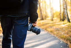 Close-up shot of a camera in photographer's hands. Man photographer from his back, walking in the park with camera in his hands. Autumn view on the background.