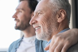 Close up shot of a caucasian young adult son supporting his old elderly senior man looking at the window in future together at home. Happy father`s day! I love you, dad!