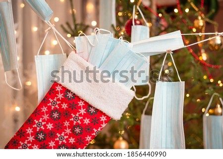 Close up shot of a christmas stocking full of protective medical masks on a garland made of masks with a christmas tree on the background. Christmas celebration during pandemic ストックフォト ©